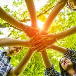 Group of friends with hands in hands with sunlight - Teamwork